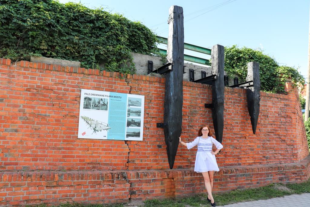 Drewniane pale dawnego mostu, za którymi kryje się kolejny mural.